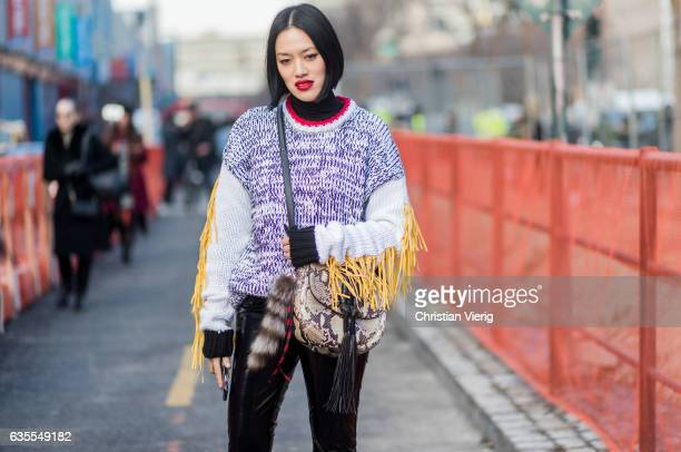 Tiffany Hsu wearing a knit snakeskin bag vinyl pants outside Yeezy Season 5 on February 15 2017 in New York City