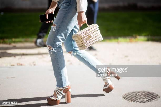 Tiffany Hsu wearing knit ripped denim jeans straw bag seen outside Moncler Gamme Rouge during Paris Fashion Week Spring/Summer 2018 on October 3 2017...