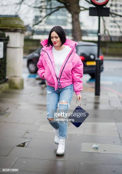 Tiffany Hsu wearing pink puffer jacket ripped denim jeans seen outside Christopher Kane during London Fashion Week February 2018 on February 19 2018...