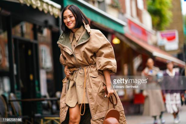Tiffany Hsu wears a beige coat with khaki inner lining, a shirt, outside JW Anderson, during London Fashion Week September 2019 on September 16, 2019...