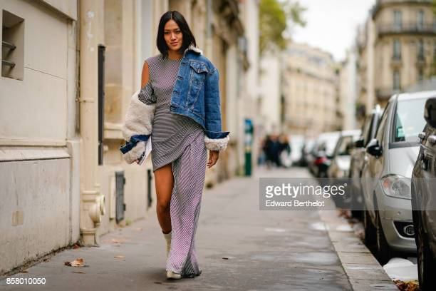 Tiffany Hsu wears a blue denim jacket with fur inner lining a black and white striped dress white shoes outside Valentino during Paris Fashion Week...