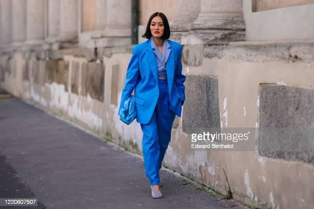 Tiffany Hsu wears a blue oversized blazer jacket, a blue leather The Pouch Bottega Veneta bag, blue pants, sandals, outside Koche x Pucci, during...