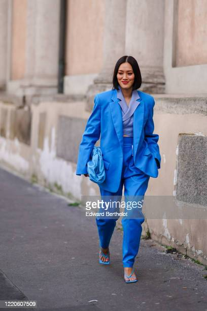 Tiffany Hsu wears a blue oversized blazer jacket, a blue leather The Pouch Bottega Veneta bag, blue pants, sandals, outside Koche x Pucci, during...