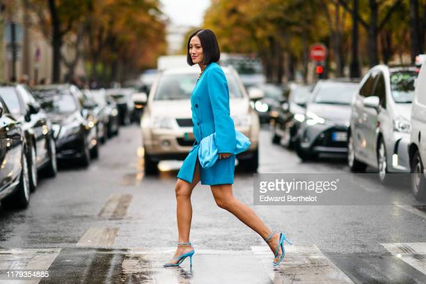 Tiffany Hsu wears a blue oversized jacket dress, a blue bag, blue heels shoes, outside Miu Miu, during Paris Fashion Week - Womenswear Spring Summer...