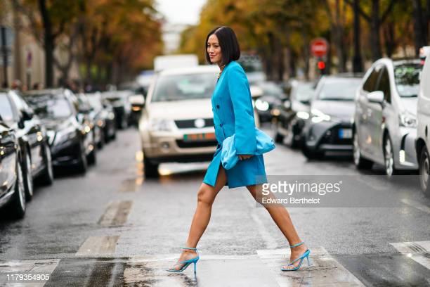 Tiffany Hsu wears a blue oversized jacket dress, a blue bag, blue heels shoes, outside Miu Miu, during Paris Fashion Week - Womenswear Spring Summer...
