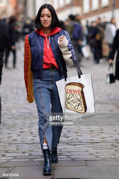 Tiffany Hsu wears a bomber jacket a red hoodie a Loewe bag with a printed toast outside Simone Rocha during London Fashion Week September 2017 on...