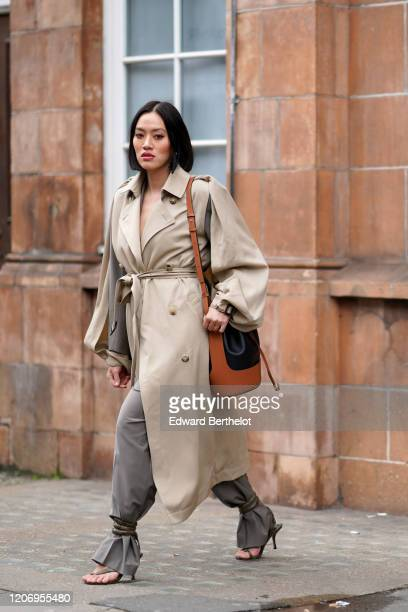 Tiffany Hsu wears a brown bag, a gray and beige trench coat, gray pants, shoes, outside GW Anderson, during London Fashion Week February 2020 on...