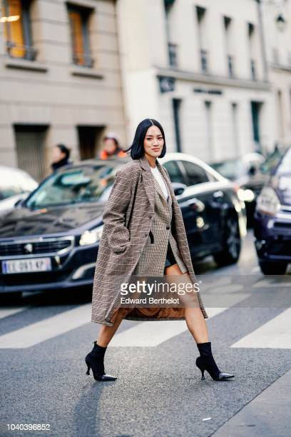 Tiffany Hsu wears a checked coat a checked blazer jacket a white top black boots outside Ellery during Paris Fashion Week Womenswear Spring/Summer...