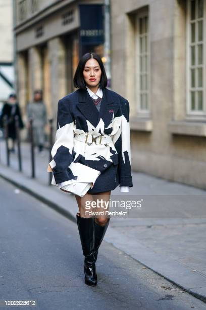 Tiffany Hsu wears a dark blue and white oversized jacket/dress, a white belt, a white clutch, black thigh high boots, outside Maison Margiela, during...