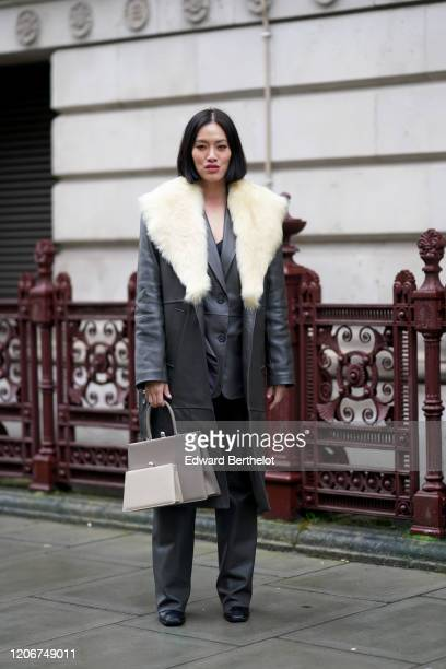 Tiffany Hsu wears a dark grau long leather coat with white faux fur a gray double bag flared pants black shoes during London Fashion Week Fall Winter...