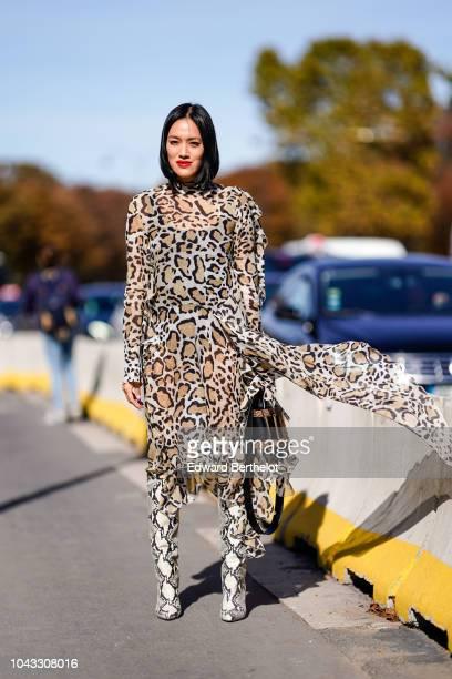 Tiffany Hsu wears a leopard print dress snake print boots a bag outside Elie Saab during Paris Fashion Week Womenswear Spring/Summer 2019 on...