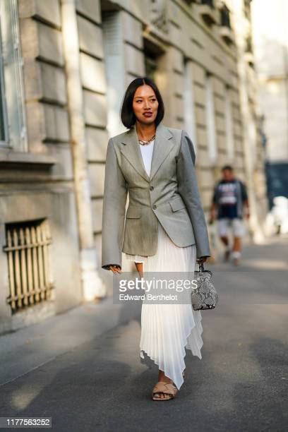 Tiffany Hsu wears a necklace, a white top, a light grey jacket, a white asymmetric handkerchief-hem pleated skirt, camel woven leather mules, a black...