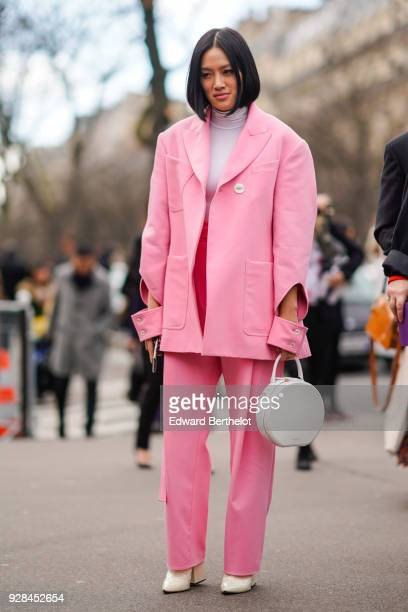 Tiffany Hsu wears a pink suit blazer jacket a white round bag a turtleneck outside Miu Miu during Paris Fashion Week Womenswear Fall/Winter 2018/2019...
