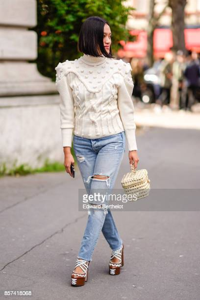 Tiffany hsu wears a pull over ripped jeans outside Moncler during Paris Fashion Week Womenswear Spring/Summer 2018 on October 3 2017 in Paris France
