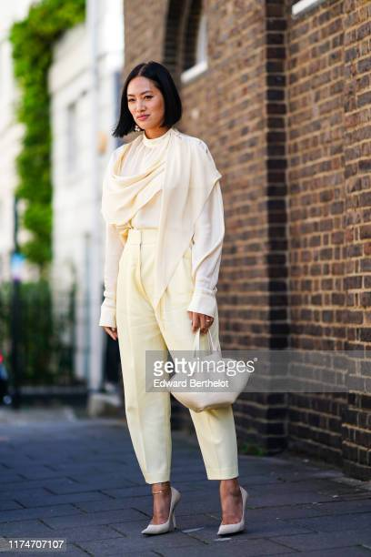 Tiffany Hsu wears a scarf, a white flowy top, pale yellow cropped pants, white heels shoes, a bag, during London Fashion Week September 2019 on...