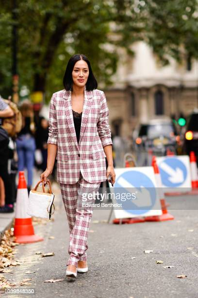 Tiffany Hsu wears a tartan checked blazer jacket suit pants a white bag during London Fashion Week September 2018 on September 18 2018 in London...