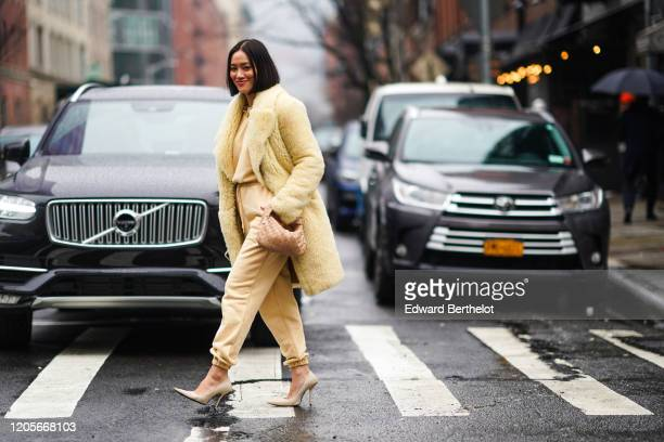 Tiffany Hsu wears a yellow fluffy coat, a woven bag, yellow pants, pointy shoes, a pale yellow top, during New York Fashion Week Fall Winter 2020, on...