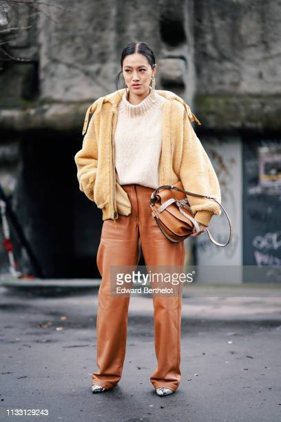 Tiffany Hsu wears a yellow fluffy jacket, a wool pullover, orange flare pants, snake print shoes, a leather bag, outside Balmain, during Paris...