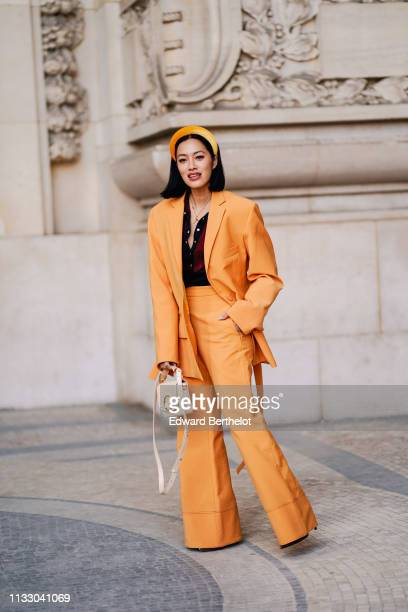 Tiffany Hsu wears an orange hairband a burgundy top an orange pantsuit with high waist flare pants a white Chloé bag outside Paco Rabanne during...