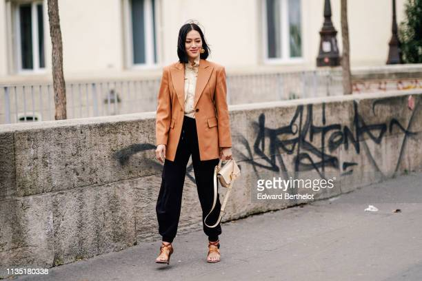 Tiffany Hsu wears earrings a beige ruffled shirt a camel coat black pants a beige Chloé bag beige and brown Chloé sandals outside Atlein during Paris...