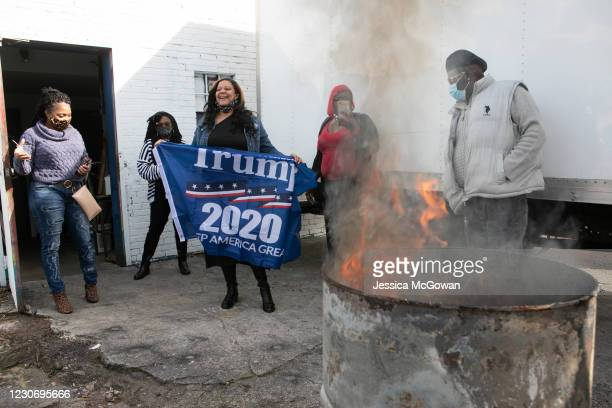 Tiffany Lumpkins burns a Trump flag during a watch party of the televised Presidential Inauguration ceremony at Tree House Lounge on January 20, 2021...