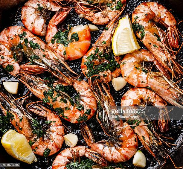 Tiger prawns roasted on frying pan with green sauce close up