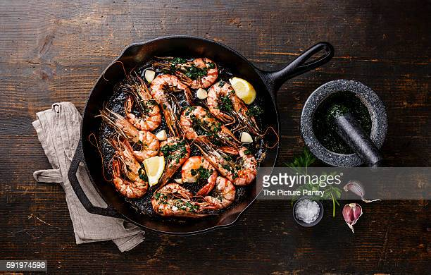 Tiger prawns shrimps roasted on frying pan with green sauce, lemon and garlic on wooden background