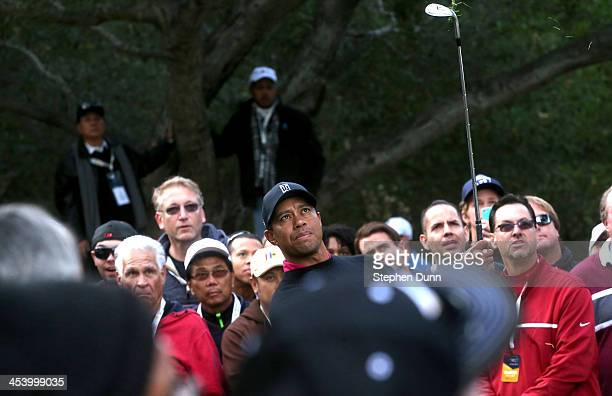 Tiger Wood watches his chip shot on the fifth hole after his second shot went into gallery during the second round of the Northwestern Mutual World...