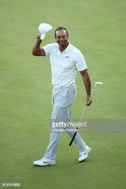 Tiger Woods acknowledges fans after finishing his round on the 18th green during the second round of the Genesis Open at Riviera Country Club on...