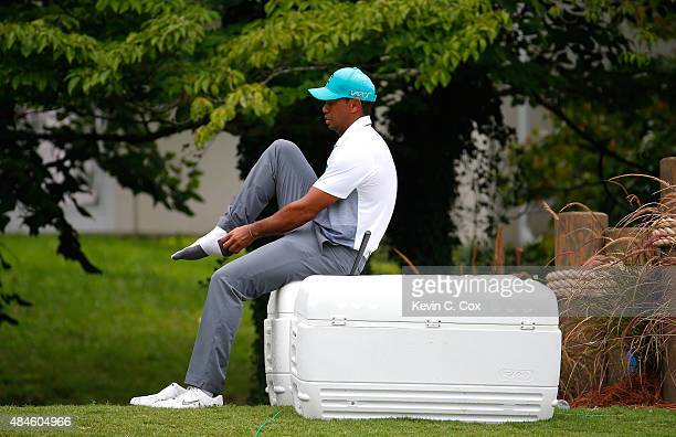 Tiger Woods adjusts his sock on the way to the ninth tee during the first round of the Wyndham Championship at Sedgefield Country Club on August 20...