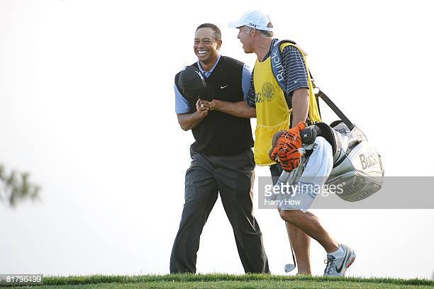 Tiger Woods alongside caddie Steve Williams reacts after holing out from the rough for birdie on the 17th hole during the third round of the 108th US...