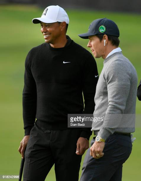 Tiger Woods and actor/singer Mark Wahlberg watch play on the ninth hole during the ProAm round for the Genesis Open at Riviera Country Club on...