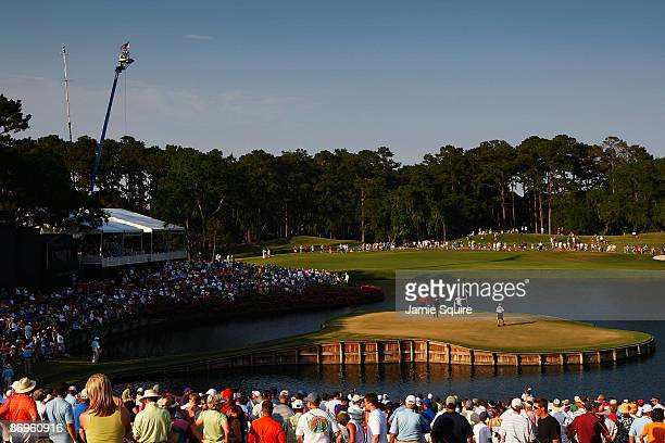 Tiger Woods and Alex Cejka of Germany are seen with their caddies on the green of the 17th hole during the final round of THE PLAYERS Championship on...