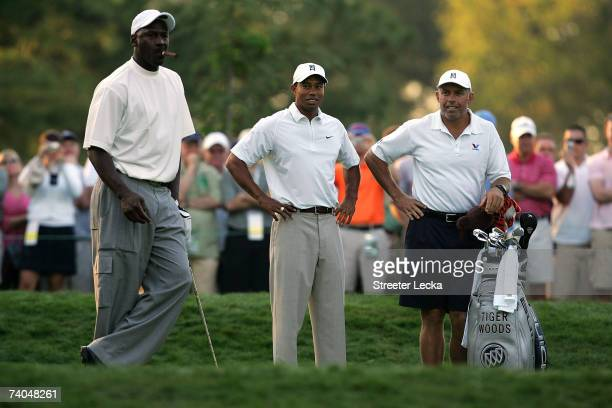 Tiger Woods and caddie Steve Williams look over at basketball star Michael Jordan on the 6th tee during the Proam at the Wachovia Championship at...