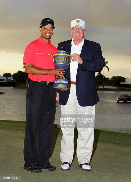 Tiger Woods and Donald Trump pose with the winner's trophy after the final round of the World Golf ChampionshipsCadillac Championship at TPC Blue...