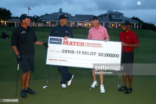 Tiger Woods and former NFL player Peyton Manning celebrate defeating Phil Mickelson and NFL player Tom Brady of the Tampa Bay Buccaneers on the 18th...