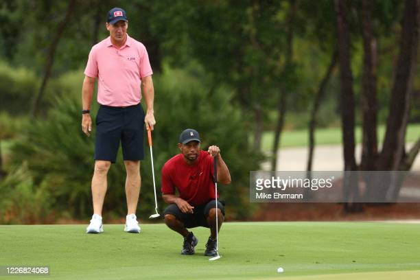 Tiger Woods and former NFL player Peyton Manning read a putt on the sixth green during The Match: Champions For Charity at Medalist Golf Club on May...