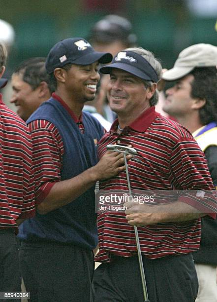 Tiger Woods and Fred Couples of the US team smile and hug after the 18th hole of the fourball matches in the third round of The Presidents Cup at...