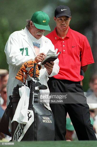 Tiger Woods and his caddie Mike 'Fluff' Cowan study the course statistics on the fourth tee 13 April during the final round of the Masters tournament...