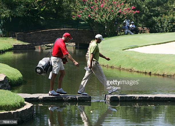 Tiger Woods and his caddie Steve Williams cross a bridge on the sixth hole during the third round of the 89th PGA Championship at the Southern Hills...
