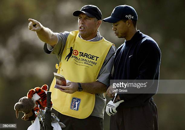 Tiger Woods and his caddie Steve Williams discuss a shot during the first round of the Target World Challenge on December 11 2003 at the Sherwood...