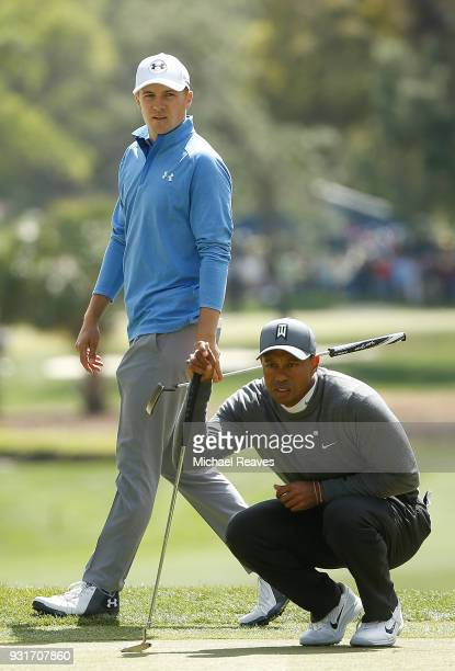 Tiger Woods and Jordan Spieth look over a putt on the second hole during the first round of the Valspar Championship at Innisbrook Resort Copperhead...