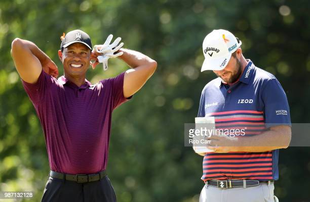 Tiger Woods and Marc Leishman of Australia speak on the 18th green during the second round of the Quicken Loans National at TPC Potomac on June 29...
