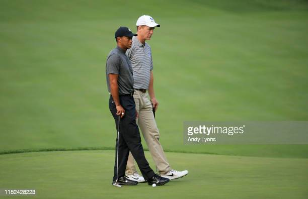 Tiger Woods and Peyton Manning wait to putt on the second hole during the Pro Am of The Memorial Tournament presented by Nationwide at Muirfield...