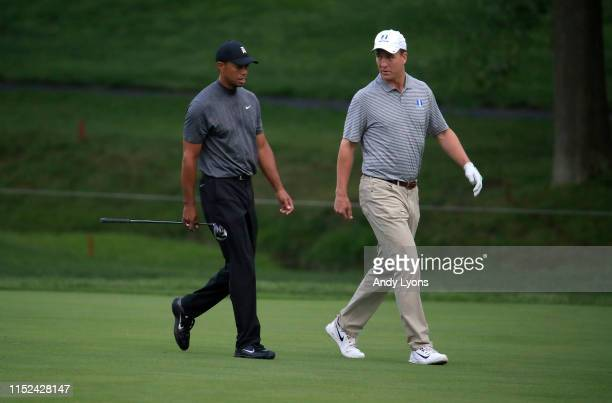 Tiger Woods and Peyton Manning walk down the fairway on the first hole during the Pro Am of The Memorial Tournament presented by Nationwide at...