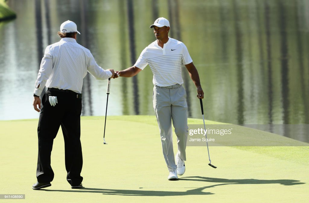Tiger Woods and Phil Mickelson of the United States fist bump during a practice round prior to the start of the 2018 Masters Tournament at Augusta National Golf Club on April 3, 2018 in Augusta, Georgia.
