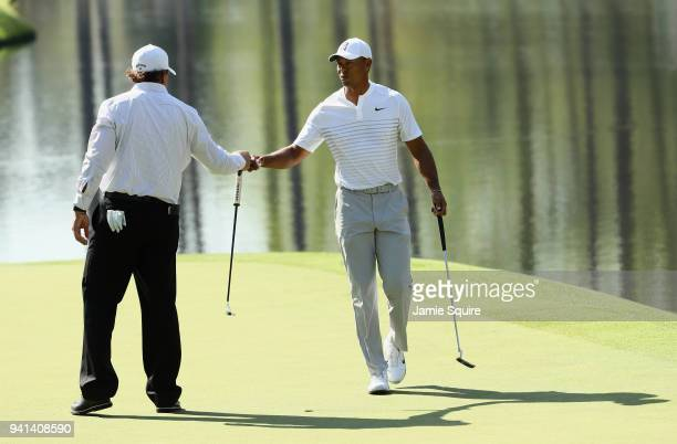 Tiger Woods and Phil Mickelson of the United States fist bump during a practice round prior to the start of the 2018 Masters Tournament at Augusta...