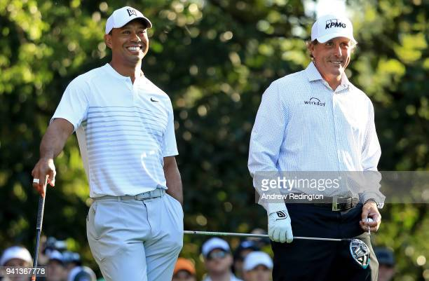 Tiger Woods and Phil Mickelson of the United States talk on the 11th hole during a practice round prior to the start of the 2018 Masters Tournament...
