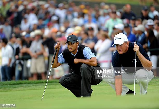 Tiger Woods and Robert Karlsson line up a putt during the third round of the 108th US Open at the Torrey Pines Golf Course on June 14 2008 in San...