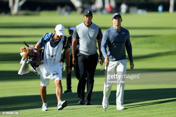 Tiger Woods and Rory McIlroy of Northern Ireland walk across the 17th hole during the first round of the Genesis Open at Riviera Country Club on...